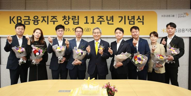 KB Financial Group Chairman Yoon Jong-kyoo, fifth from left, poses with employees during the group's 11th anniversary at the firm's headquarters on Yeouido, Seoul, Friday. / Courtesy of KB Financial Group