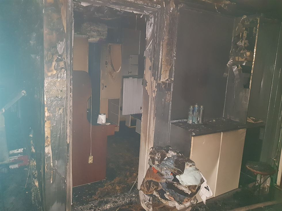 Firefighters move inside the apartment after putting out the fire. They found two bodies inside a refrigerator that had tumbled on its side in the middle of the living room in Cheonan, South Chungcheong Province. Yonhap