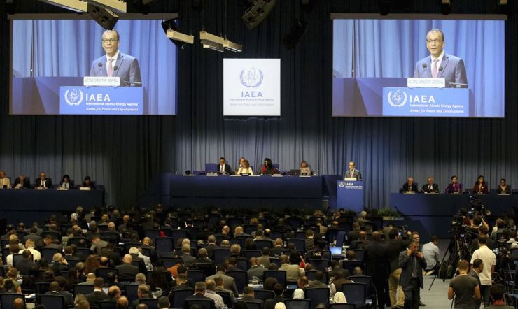 Acting Director General of the International Atomic Energy Agency (IAEA) Cornel Feruta is seen on screens as he delivers a speech during the general conference of the IAEA at the International Center in Vienna, Austria, Monday, Sept. 16, 2019. AP