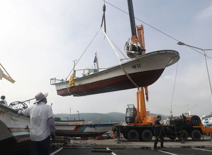 A fishing boat is lifted onto land at a port in Ulsan on Thursday to take shelter from powerful Typhoon Lingling that is expected to slam into the Korean Peninsula on Saturday. Yonhap