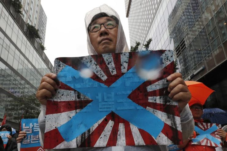South Korean protesters hold Japanese rising sun flags during a rally to mark the Aug. 15 Liberation Day from Japanese colonial rule, in downtown Seoul. Korea asked the International Olympic Committee to ban the Japanese 'rising sun' flag at 2020 Tokyo Games, calling it a symbol of Japan's brutal wartime past. AP