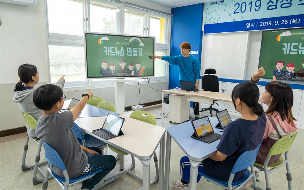 The head of Byeolmaro Library poses with students in Yeongwol, Gangwon Province, after the library was chosen as an institution to benefit from Samsung Electronics' smart school support program, Sept. 26. / Courtesy of Samsung Electronics