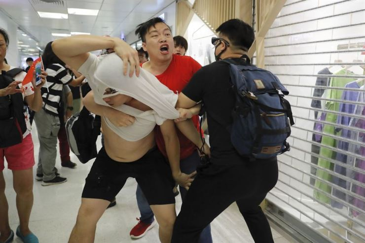 A Pro-China supporter, in red, and anti-government protesters fight at Amoy Plaza in the Kowloon Bay district in Hong Kong, Saturday, Sept. 14, 2019. AP-Yonhap