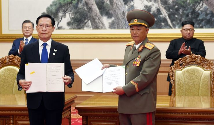 South Korea's then-Defense Minister Song Young-moo, left and North Korean Minister of the People's Armed Forces No Kwang-chol show reporters the Comprehensive Military Agreement signed by the two in the presence of President Moon Jae-in and North Korean leader Kim Jong-un in this Sept. 19, 2018, file photo. Joint Press Corps