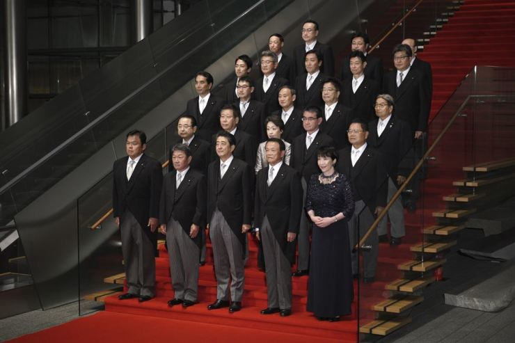 Japanese Prime Minister Shinzo Abe, front row center, poses with his new cabinet, for a group photo session at the prime minister's official residence in Tokyo, Sept. 11. Abe reshuffled his Cabinet on Wednesday, adding two women and the son of a former leader to freshen his image but maintaining continuity on U.S.-oriented trade and security policies. AP-Yonhap