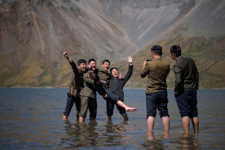 In a photo taken on Sept. 11, 2019, North Korean students pose for photos in Chonji lake, or 'heaven lake,' as they visit the crater of Mount Paektu, near Samjiyon. Mount Paektu has long been considered the spiritual birthplace of Korea. AFP
