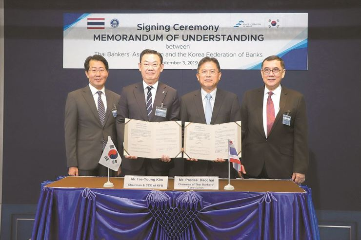 Korea Federation of Banks (KFB) Chairman and CEO Kim Tae-young, second from left, holds an MOU with Thai Bankers' Association (TBA) Chairman Predee Daochai, alongside officials from the Korea Development Bank and the TBA in Bangkok, Thailand, Sept. 3. The two sides agreed to boost cooperation and exchanges in the financial sector. Courtesy of KFB