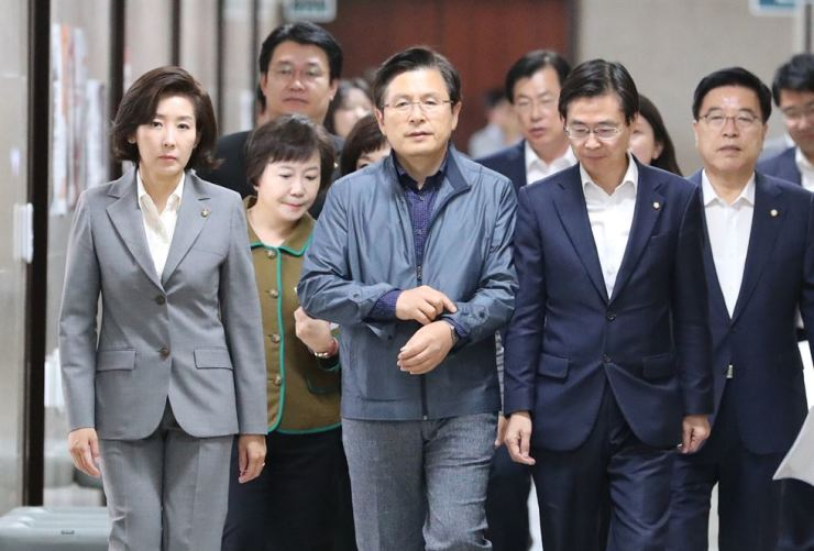 Hwang Kyo-ahn, center, leader of the main opposition Liberty Party Korea, walks with key party members in the corridor of the National Assembly on Monday. Yonhap