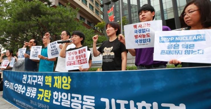 A group of activities stage a protest against Japan's plan to leak contaminated water into the sea in front of former Japanese embassy in Seoul, on Aug. 16. Yonhap