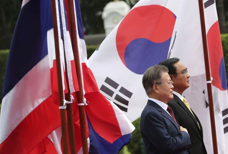 South Korean President Moon Jae-in, left, and Thailand's Prime Minister Prayuth Chan-o-cha listen to their national anthems during a welcoming ceremony at the government house in Bangkok, Thailand, Sept. 2. AP-Yonhap