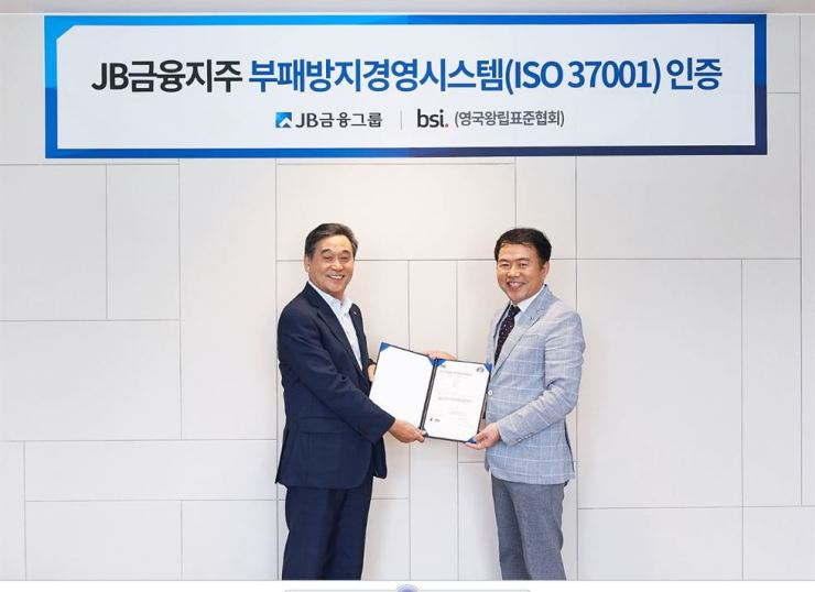 JB Financial Group Chairman Kim Ki-hong, left, receives ISO 37001 certification from BSI Korea lead auditor Song Kyung-soo at the JB Building in Seoul, Friday. / Courtesy of JB Financial Group