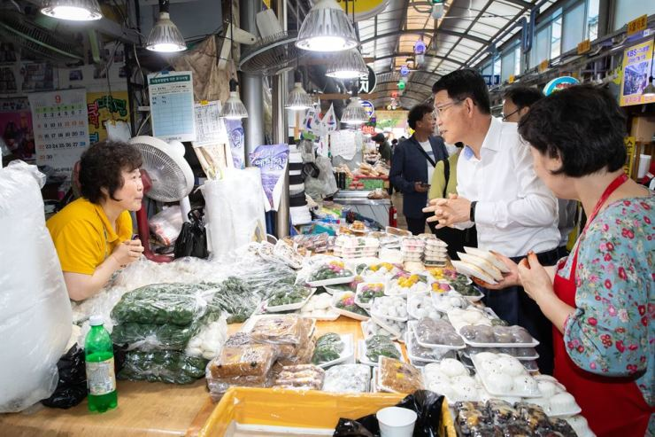 Financial Services Commission (FSC) Chairman Eun Sung-soo talks with merchants at Yeongcheon Traditional Market in western Seoul, Tuesday, to listen to their difficulties ahead of the Chuseok long weekend that falls between Thursday and Sunday. Eun, who took office Monday, vowed to stabilize the financial market and encourage innovation. / Courtesy of FSC