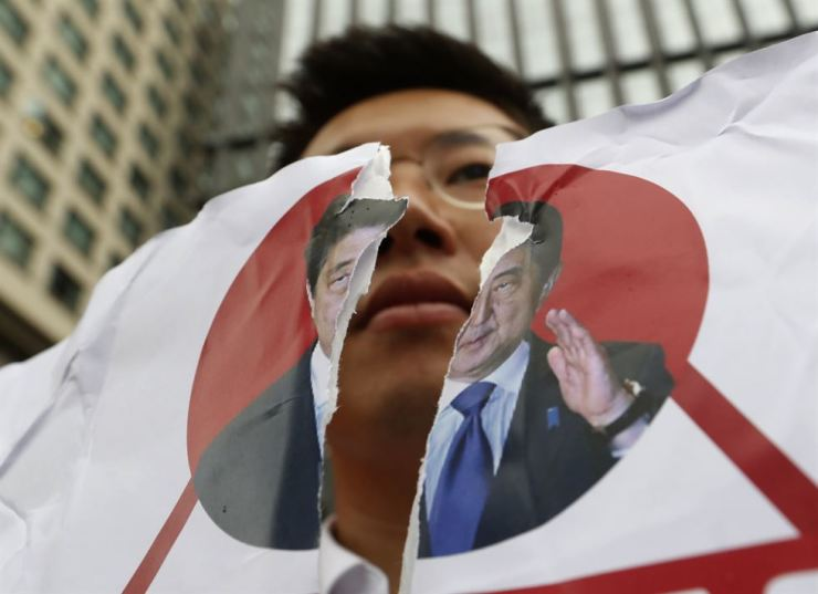 A protester holds a defaced image of Japanese Prime Minister Shinzo Abe during a rally denouncing the Japanese government's decision on their exports to South Korea in front of the Japanese Embassy in Seoul, July 17. On Wednesday, Korea removed Japan from its list of trusted trade partners. AP