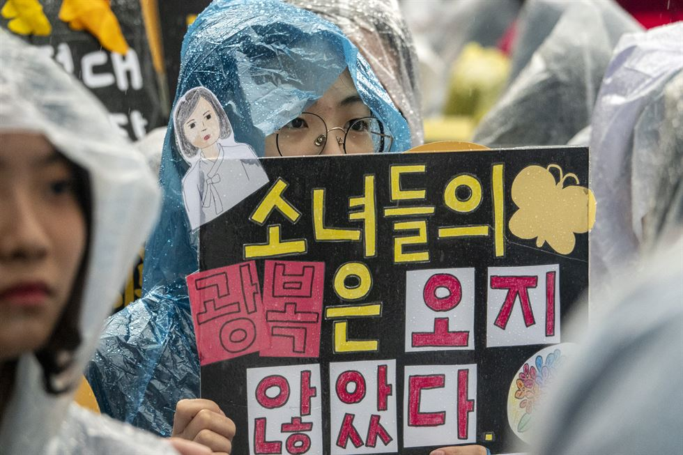Amid lingering Seoul-Tokyo tension over trade, security and history, Koreans gathered in front of the former Japanese Embassy in Seoul's Jongno District Wednesday to show their support for the Korean victims of sex slavery by the Japanese imperial army during World War II. The weekly street demonstration, urging the Japanese government to issue a fresh apology to the surviving victims and ways to compensate them, has notched its 1,403rd occasion. A bronze statue of a 'comfort woman,' which symbolizes the victims, is surrounded by the day's protesters in a downpour. Korea Times photo by Shim Hyun-chul