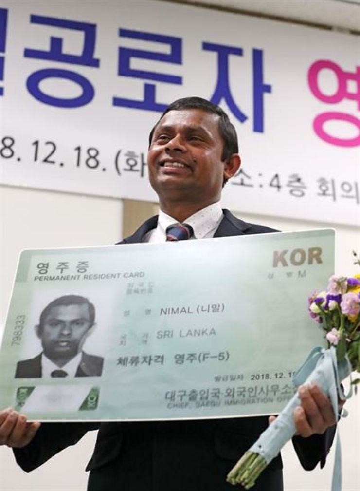 A Sri Lankan holds an enlarged version of the current design of the F-5 permanent resident card at Daegu Immigration Office on Dec. 18, 2018. He was granted the status after saving an elderly woman from a fire. / Yonhap
