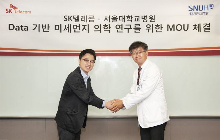 Hong Seung-jin, left, who heads the AI home unit at SK Telecom, shakes hands with Prof. Lee Chang-hyun, a radiologist at Seoul National University Hospital, at the mobile carrier's head office in Seoul, Thursday, after signing a MOU for a study on fine dust. / Courtesy of SK Telecom