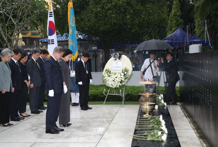 President Moon Jae-in and first lady Kim Jung-sook hold a moment of silence in front of a stone monument at the Martyrs' Mausoleum in Yangon, Myanmar, Wednesday, that commemorates South Korean victims of an Oct. 9 1983 bombing attack by North Korean agents aimed at assassinating then South Korean President Chun Doo-hwan. Yonhap