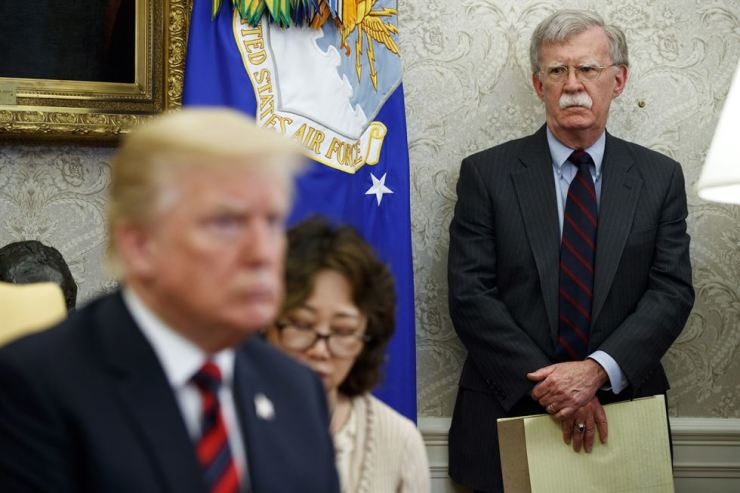 In this May 22, 2018, file photo, U.S. President Donald Trump, left, meets with South Korean President Moon Jae-In in the Oval Office of the White House in Washington, as national security adviser John Bolton, right, watches. Trump says he fired national security adviser John Bolton, says they 'disagreed strongly' on many issues. AP-Yonhap