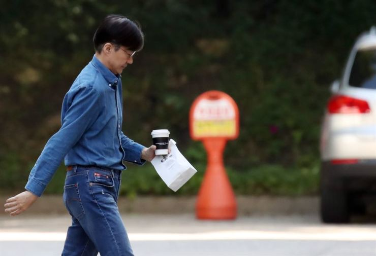 Justice Minister Cho Kuk, in casual outfit, walks toward his apartment in Bangbae-dong, southern Seoul, Sunday. Prosecutors are expected to summon his wife, Chung Kyung-shim, this week to question over alleged illegal acts involving Cho and his family members. Yonhap