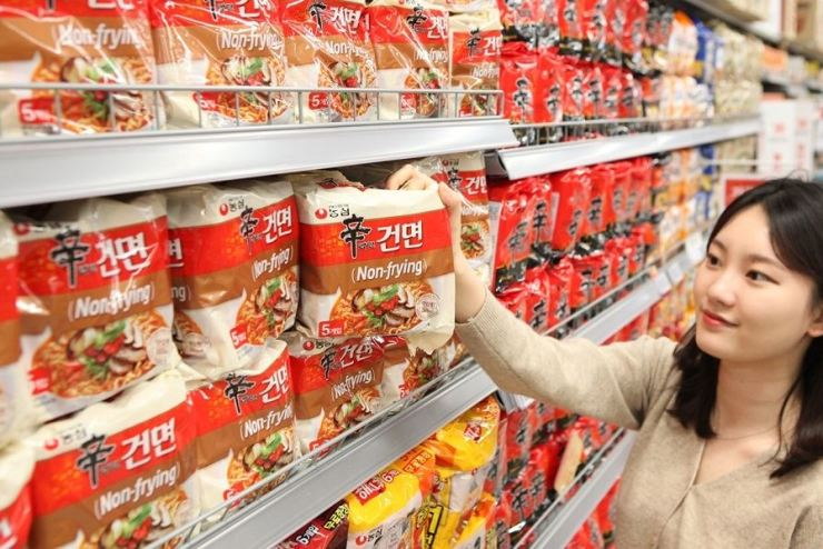 A customer picks up Korean instant noodles at a supermarket in Seoul. Korea Times file