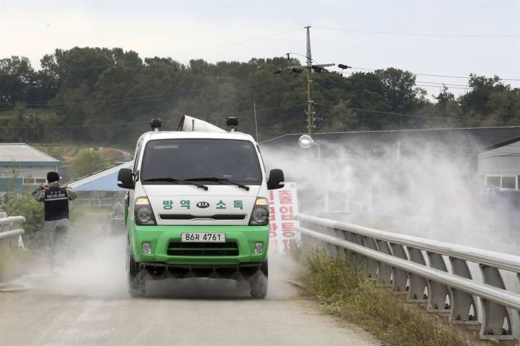 Disinfectant solution is sprayed from a vehicle as a precaution against African swine fever near a pig farm in Paju, Friday, Sept. 20, 2019. AP