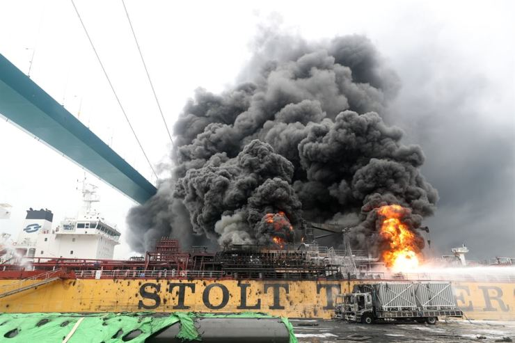 Firefighters try to put out the fire on the ship after an explosion at a port of Ulsan, South Gyeongsang Province, Saturday. Yonhap