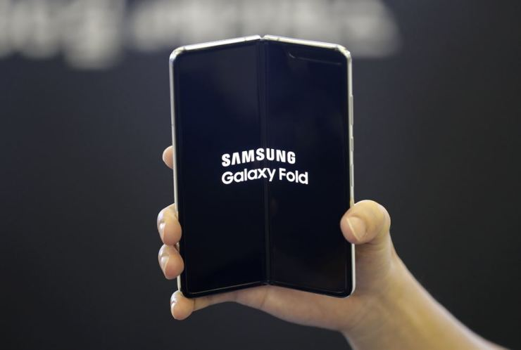 In this Sept. 6, 2019, file photo, an employee holds the Samsung Electronics's Galaxy Fold for a photo at a shopping mall in Seoul. AP