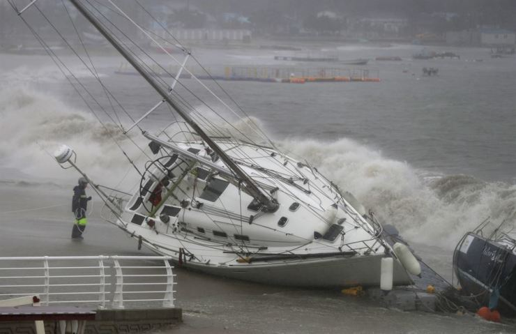 Strong winds and waves from Typhoon Tapah drive two boats ashore in the southern city of Ulsan, Sunday. / Yonhap