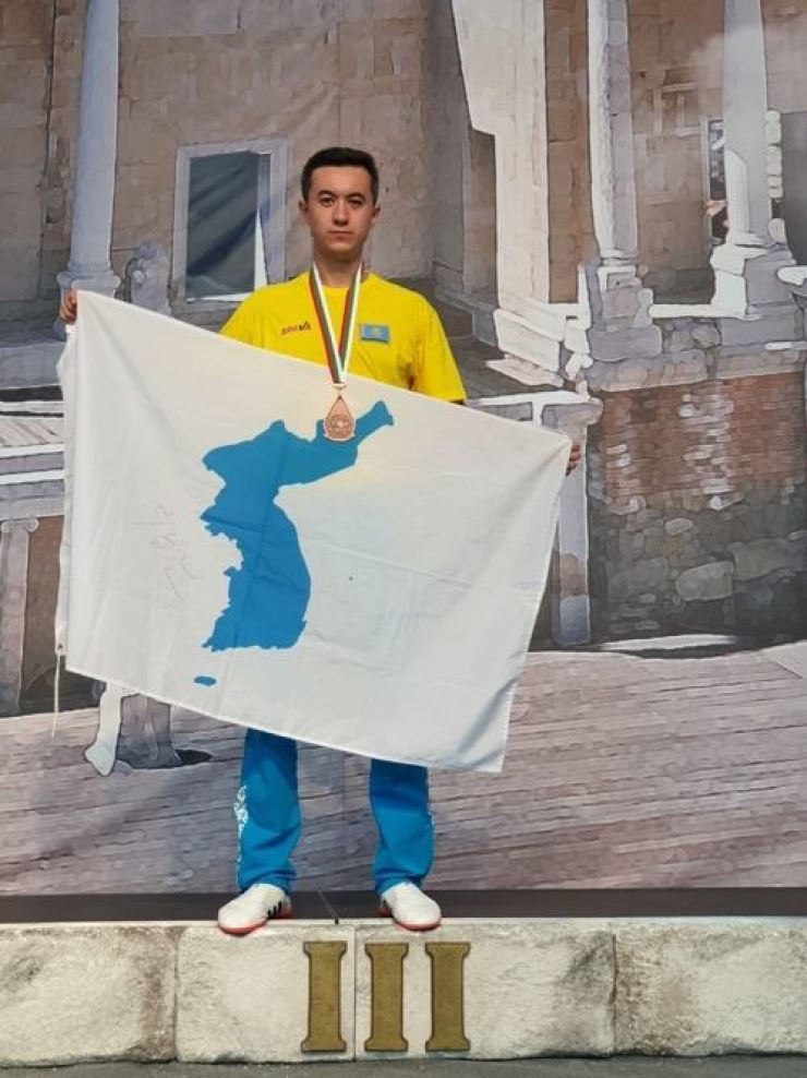 Ethnic Korean Ilya Hwang from Kazakhstan poses with a unified Korean flag after coming third in the men's technical skills category at the ITF World Championship last month in Plodiv, Bulgaria. / Yonhap