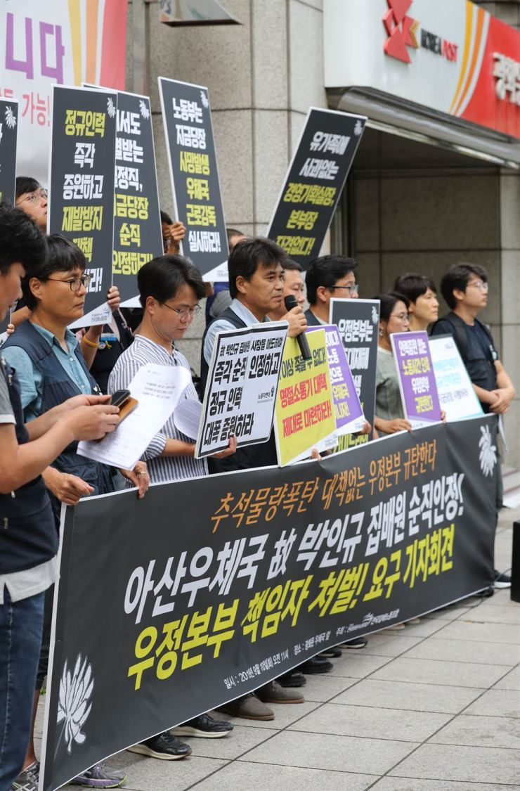 Members of the Korea Postal Workers Union stage a rally in front of Gwanghwamun Post Office in central Seoul, Tuesday, calling on the Korea Post to take responsibility for the death of Park In-kyu, a postal worker who died in a traffic accident while delivering parcels last Friday, claiming his death was caused by a heavy workload ahead of the Chuseok holiday. /Yonhap