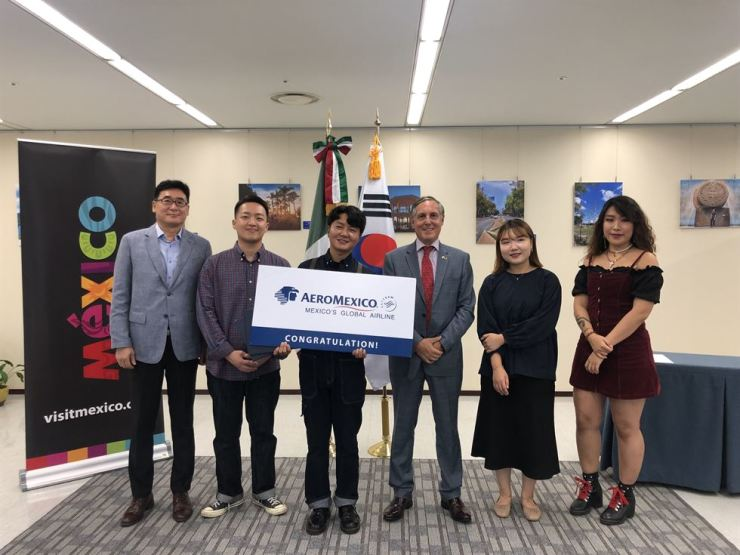 Mexican Ambassador to Korea Bruno Figueroa, third from right, and Aeromexico Korea Director Shin Yong-jin, left, pose with winners of the 2nd University Photo Contest: Mexico, A World of its Own during an award ceremony at the Embassy of Mexico in Korea, Sept. 10. / Embassy of Mexico