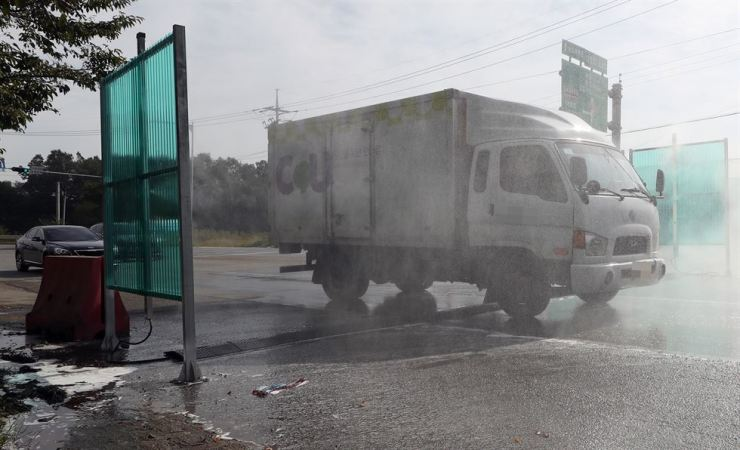 A truck is doused with disinfectant solution to prevent the spread of African swine fever on a road in Gimpo, Gyeonggi Province, Thursday. Local governments, especially in regions affected by the disease, have been canceling their autumn festivals to prevent it from spreading. / Yonhap