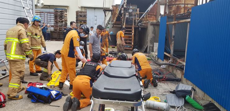 Rescue personnel try to resuscitate foreign workers who fell unconscious while cleaning a tank at fish processing company in Yeongdeok, North Gyeongsang Province, Tuesday. Courtesy of North Gyeongsang Fire Station