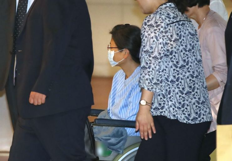 Former President Park Geun-hye, in a wheelchair, is escorted into Seoul St. Mary's Hospital in southern Seoul on Monday morning. She will undergo a surgery for rotator cuff tear on her left shoulder on Tuesday. Yonhap