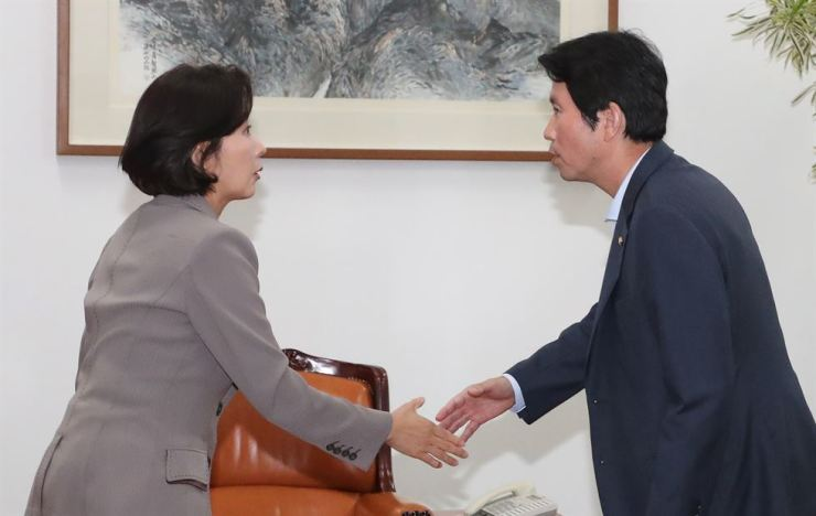 Rep. Na Kyung-won, left, floor leader of the main opposition Liberty Korea Party, and Rep. Lee In-young, floor leader of the ruling Democratic Party of Korea, shake hands before having a meeting over a confirmation hearing in the National Assembly for Justice Minster nominee Cho Kuk at the National Assembly, Wednesday.