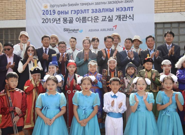 Asiana Airlines officials pose with students of an elementary school in Ulaanbaatar, Mongolia, Wednesday, after helping the school remodel its gym as part of its Beautiful Classroom corporate social responsibility project. The remodeling marks the start of the project in the country after the airline launched flights to Ulaanbaatar in July. / Courtesy of Asiana Airlines