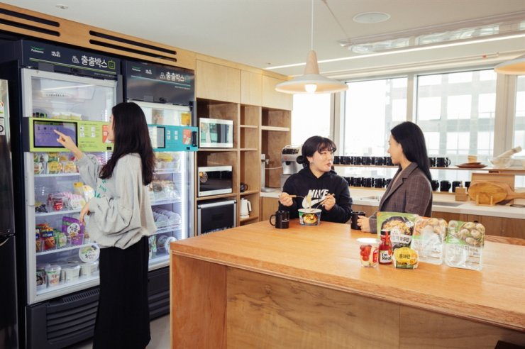 Pulmuone officials test a frozen food vending machine installed at a share house in Gangnam-gu, Seoul, Friday. The food firm said the vending machine is able to showcase not only room temperature foods but also cold and frozen foods, thus offering more various choices for share house residents who prefer home meal replacements. Courtesy of Pulmuone