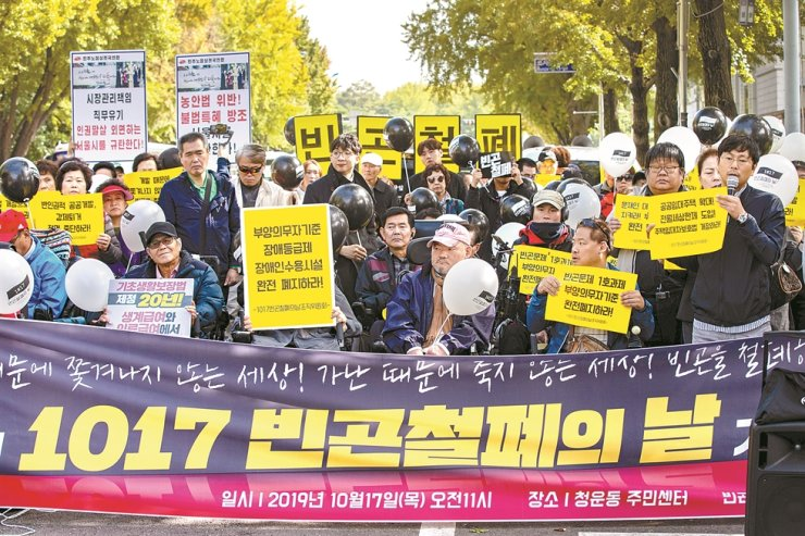 Civic groups and people in need call on the government to expand the social security net for the poor and the disabled, during a press conference near Cheong Wa Dae, Seoul, Thursday, the U.N.-designated International Day for the Eradication of Poverty. Korea Times photo by Shim Hyun-chul