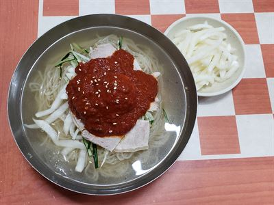 Milmyeon is made with a mixture of flour and starch dough and is served with red spicy sauce on top, along with chopped cucumber, thin-sliced beef and pickled radish. Gettyimagesbank
