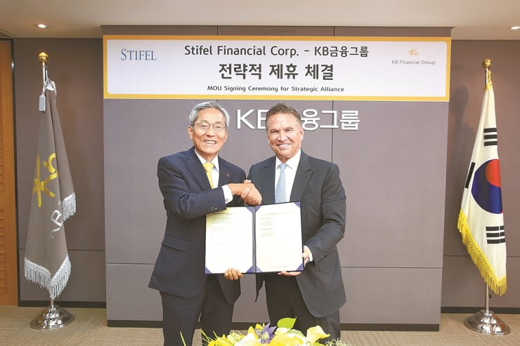 KB Financial Group Chairman Yoon Jong-kyoo, left, shakes hands with Stifel Financial Corp. Chairman Ron Kruszewski, after signing a memorandum of understanding to form a strategic alliance at the group headquarters on Yeouido, Seoul, Oct. 21. Courtesy of KB Financial Group