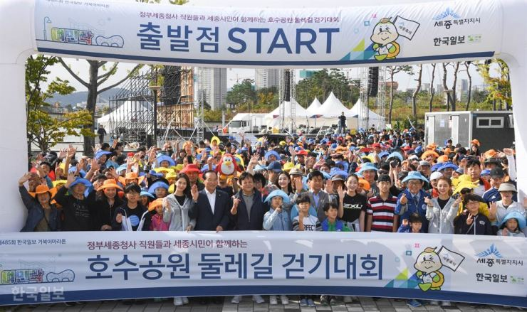 Turtle Marathon: Participants in the 485th Turtle Marathon organized by the Hankook Ilbo, the sister paper of The Korea Times, and VIPs pose for a photo before the walkathon begins at Sejong's Lake Park, Sunday. The VIPs included, Rep. Kim Joong-ro, seventh from left in the front row, of the minor opposition Bareun Mirae Party; Lee Joon-hee, to Kim's left, president of the Hankook Ilbo; Sejong Mayor Lee Chun-hee, 11th from left; and Choi Kyo-jin, 15th from left, Sejong city's chief education officer. Korea Times photo by Ryu Hyo-jin