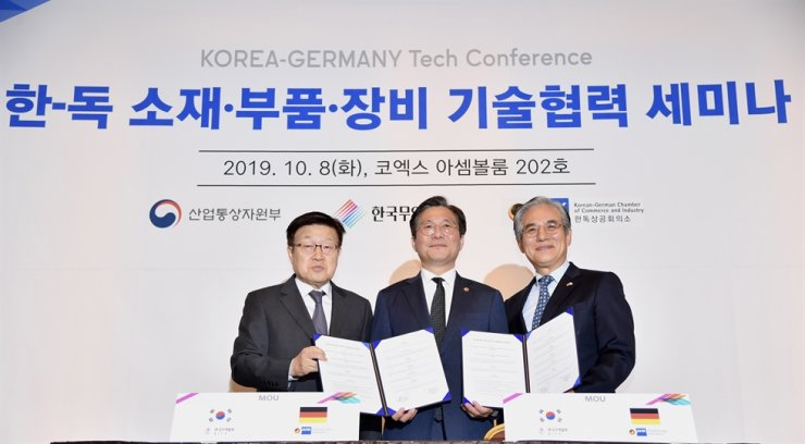 Kim Hyo-joon, right, chairman of the Korean-German Chamber of Commerce and Industry, and BMW Korea, Industry Minister Sung Yun-mo, center, and Korea International Trade Association Chairman Kim Young-ju pose at COEX in southern Seoul, Tuesday, after signing a memorandum of understanding to strengthen partnerships between Korean and German companies. Courtesy of Korea International Trade Association
