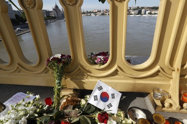 In this Saturday, June 1, 2019, file photo, flowers and flag of Korea are laid on the Margit Bridge where a sightseeing boat capsized in Budapest. Hungarian officials have finished their investigation of a boat crash on the Danube River in which 28 people died. Prosecutors said they would review the gathered information before deciding how to proceed with the case. AP