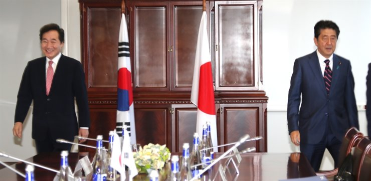 Prime Minister Lee Nak-yon, left, and Japanese Prime Minister Shinzo Abe walk to their seats before the start of a bilateral meeting held on the sidelines of the Eastern Economic Forum in Vladivostok, Russia, on Sept. 11, 2018. Yonhap