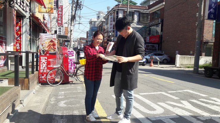 Chang Yu-jin hands out Chinese language leaflets telling Chinese-speaking residents and business owners how to dispose of trash properly in a neighborhood in Gwangjin district, eastern Seoul. / Courtesy of Gwangjin-gu Office
