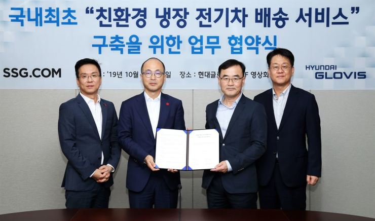 Hyundai Glovis CEO Kim Jung-hoon, right, with SSG.com CEO Choi Woo-jung, left, and other officials after signing a memorandum of understanding to supply electric delivery trucks to the retailer. / Courtesy of Hyundai Glovis