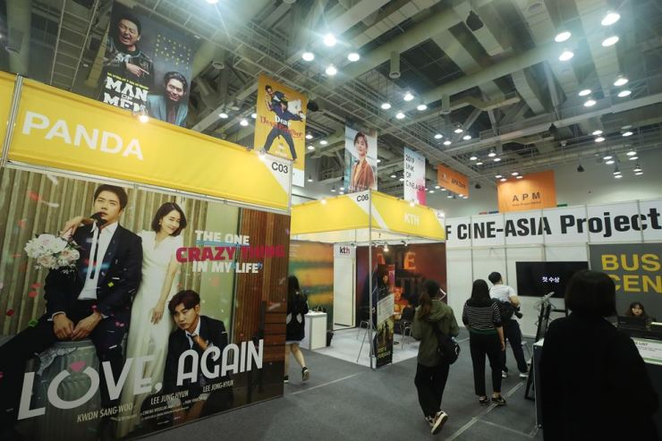 Visitors walk past cinema posters for the Busan International Film Festival at the Busan Exhibition and Convention Center in Busan, Sunday. Yonhap