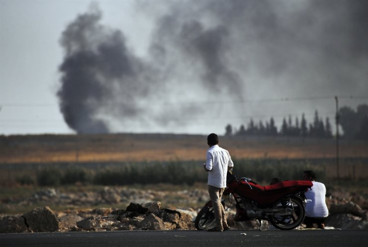 People in Akcakale, Sanliurfa province, southeastern Turkey, at the border with Syria, watch smoke billowing from targets inside Syria, during bombardment by Turkish forces, Thursday, Oct. 10, 2019. Turkey's foreign minister says Turkish troops intend to move some 30 kilometers (19 miles) deep into northern Syria and that its operation will last until all 'terrorists are neutralized,' a reference to Syrian Kurdish fighters. AP
