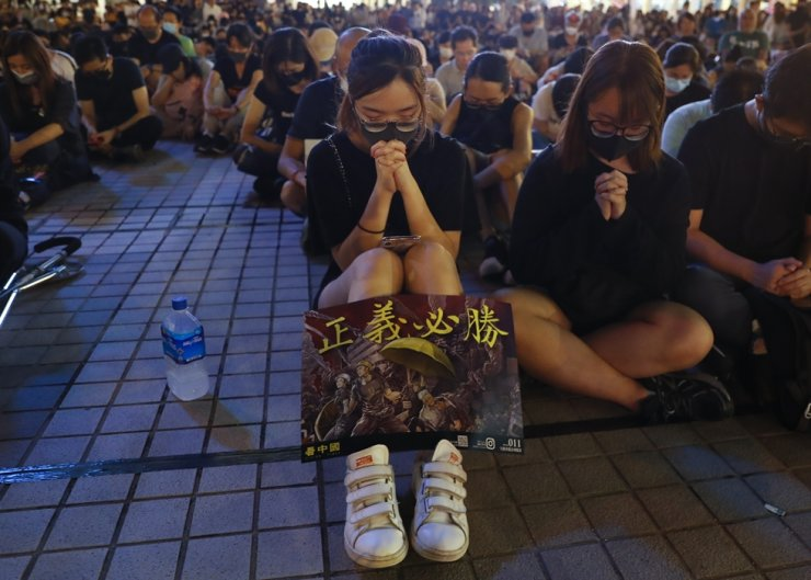 A girl puts a placard illustration on her leg as she prays during a prayer meeting for wounded protesters at Edinburgh Place in Central, Hong Kong, Oct. 19, 2019. Hong Kong has been gripped by mass demonstrations since June over a now-withdrawn extradition bill, which have since morphed into a wider anti-government movement. EPA
