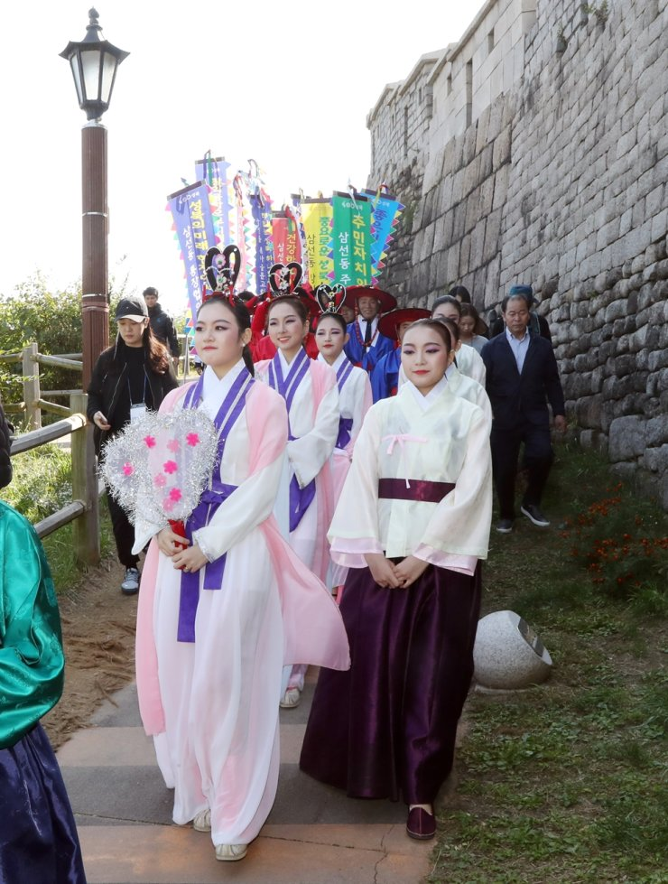 Women dressed as 'seonnyeo,' fairies that appear in Korean folk tales, walk in a procession along the old city walls at Seonnyeo Festival held in Seongbuk-gu, northeastern Seoul, Sunday. / Yonhap